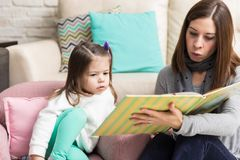 Female Parent Spending Time With Daughter. Beautiful Caucasian mother reading book to daughter while sitting at home stock photo