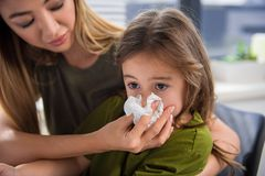 Female parent taking care of her daughter. Portrait of cut asian girl blowing snot into the napkin. Her mother is keeping it near her nose with care Stock Photography