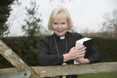 Female parish priest on a house call entering the garden gate Stock Image