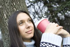 Female in a park drinking coffee Stock Image