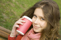 Female in a park drinking coffee Royalty Free Stock Image