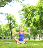 Female in a park sitting on a mat and exercising with dumbbells Stock Photography
