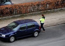FEMALE PARKING INSPECTOR CHECKING PARKING PERMISSION. Copenhagen/Denmark 31..March.2018_ .Parkin inspector from council checking parking permission at autos Stock Photography