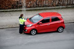 FEMALE PARKING INSPECTOR CHECKING PARKING PERMISSION. Copenhagen/Denmark 31..March.2018_ .Parkin inspector from council checking parking permission at autos Royalty Free Stock Photography