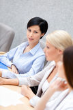 Female partners discuss business plan. Female colleagues discuss business plan sitting at the conference hall. Business cooperation Stock Photography
