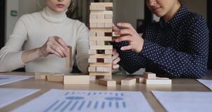 Female partners playing jenga game on office table, close up