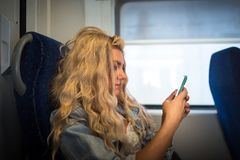 Female passenger in casual clothes sits alone inside the train stock photography