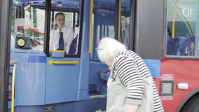 Female Passenger Helping Senior Woman To Board Bus stock footage