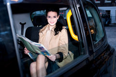 Female passenger reading newspaper inside taxi Royalty Free Stock Images