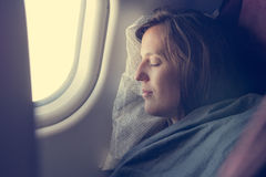 Female passenger sleeping covered with blanket. Comfortable flying Royalty Free Stock Images