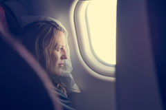 Female passenger sleeping covered with blanket. Comfortable flying Stock Photos