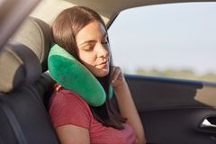 Female passenger sleeps in car while rides on long distance, uses small pillow as has pain in neck, takes nap, has rest, feels tir. Ed for being in motion much stock photo