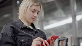 Female passenger is typing on smartphone in waiting hall, view on her face. Young blonde woman is browsing in internet by mobile phone in hall of airport or stock footage