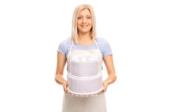 Female pastry chef carrying a large cake Royalty Free Stock Photos