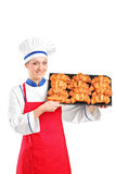 Female pastry chef holding a pan full of croissants Stock Images