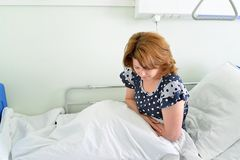 Female patient with abdominal pain on bed in hospital ward Stock Photography