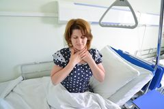 Female patient with angina on  bed in hospital ward Stock Photography