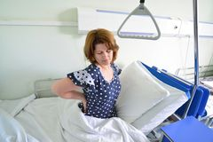 Female patient with back pain on  bed in hospital ward Stock Photo