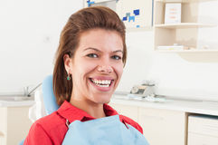Female patient with big white teeth smiling. And sitting in dentist chair Stock Photos