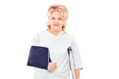 Female patient with broken arm standing with a crutch Stock Images