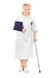 Female patient with broken arm standing with a crutch Stock Photography