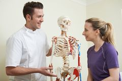 Female Patient In Consultation With Osteopath. Female Patient In Consultation With Male Osteopath Stock Image