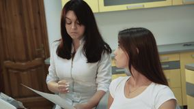Female patient consults with dentist in dental chair. 4K.  stock video
