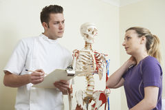 Female Patient Describing Neck Injury To Osteopath Stock Photo
