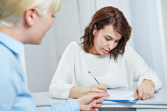 Female patient at doctor filling out form stock image