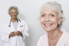 Female Patient With Doctor Holding Mobile Phone In Background Royalty Free Stock Photos