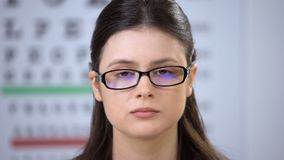Female patient in eyeglasses looking to camera and blinking, sight examination. Stock footage stock footage