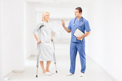 Female patient in gown with crutches and medical doctor during a. Conversation in clinical corridor Royalty Free Stock Photo