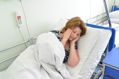 Female patient with headache on bed in hospital ward Royalty Free Stock Photo