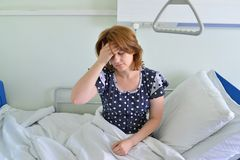 Female patient with headache on bed in hospital ward Stock Photo