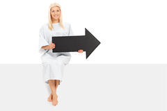 Female patient holding an arrow seated on a panel Royalty Free Stock Photos