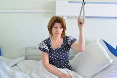 Female patient holding on to device for lifting in hospital room Royalty Free Stock Photography