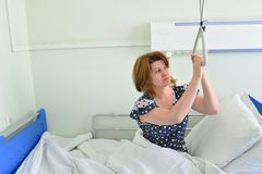 Female patient holding on to device for lifting in hospital room Stock Photo