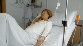 A female patient in a hospital ward with a drip stock video