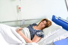 Female patient lying on  bed in hospital ward Stock Image