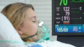 Female patient lying hospital bed with oxygen mask, monitor showing vital signs. Stock footage stock video footage