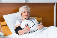 Female patient is measuring the arterial pressure using a medical equipment, while lying in the hospital bed. In the hospital ward. Healthcare concept royalty free stock photography