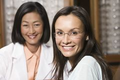 Female Patient And Optician At Optometrists. Portrait of a beautiful patient and optician at optometrists Royalty Free Stock Image