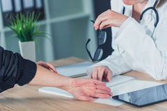 Female patient at orthopedic doctor medical exam for wrist injur Royalty Free Stock Photo