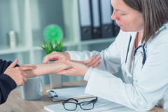 Female patient at orthopedic doctor medical exam for wrist injur. Female patient at orthopedic medical exam in doctor`s hospital office, traumatology and medical Royalty Free Stock Photo