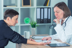 Female patient at orthopedic doctor medical exam for wrist injur. Female patient at orthopedic medical exam in doctor`s hospital office, traumatology and medical Stock Photo