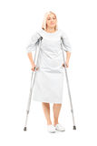 Female patient posing with crutches. Full length portrait of a female patient posing with crutches isolated on white background Royalty Free Stock Image