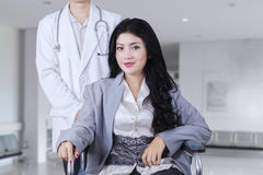 Female patient sits on wheelchair in corridor Stock Photos