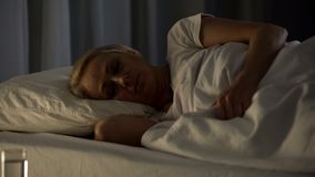 Female patient sleeping in hospital bed, health problem, retired age disability stock photography