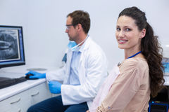 Female patient smiling at camera while dentist looking at an x-ray Royalty Free Stock Photos