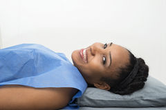 Female Patient Smiling While Lying On Bed In Clinic Royalty Free Stock Photography